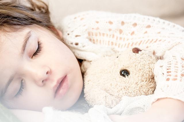 ぬいぐるみを抱えてスヤスヤと眠る赤ちゃん